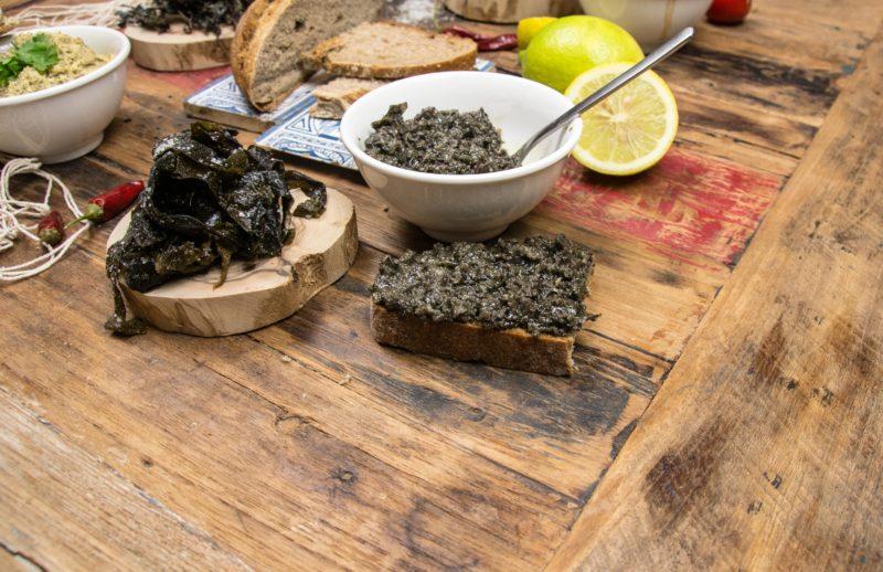 Leckere Gerichte aus frischen Algen auf einem Holztisch angerichtet.