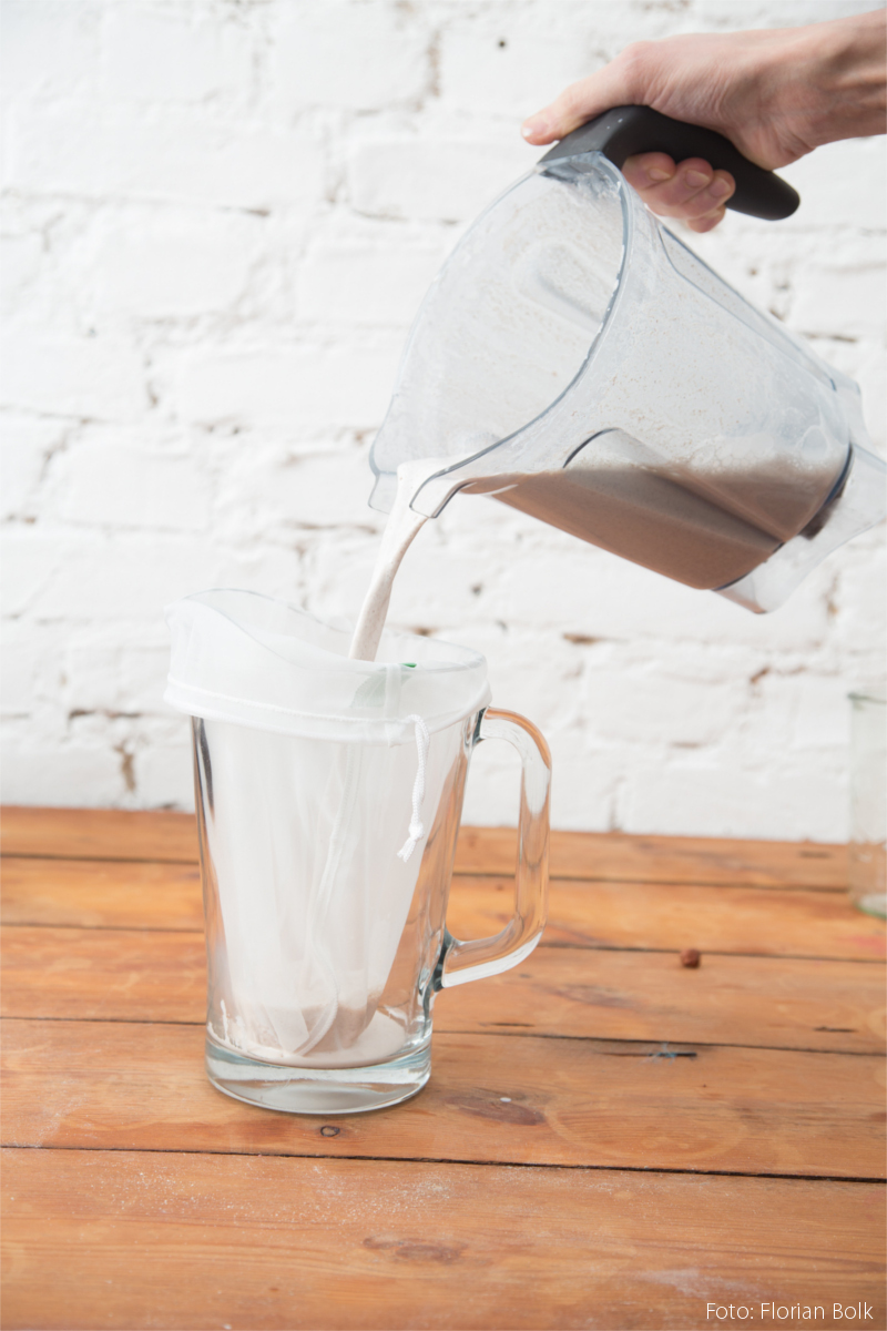 Boris Lauser schüttet Nussmilch in eine Karaffe.