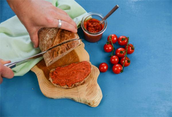 Selbstgemachte, vegane Tomatenbutter mit KULAU Bio-Kokosöl angerichtet mit Brot und frischen Tomaten.