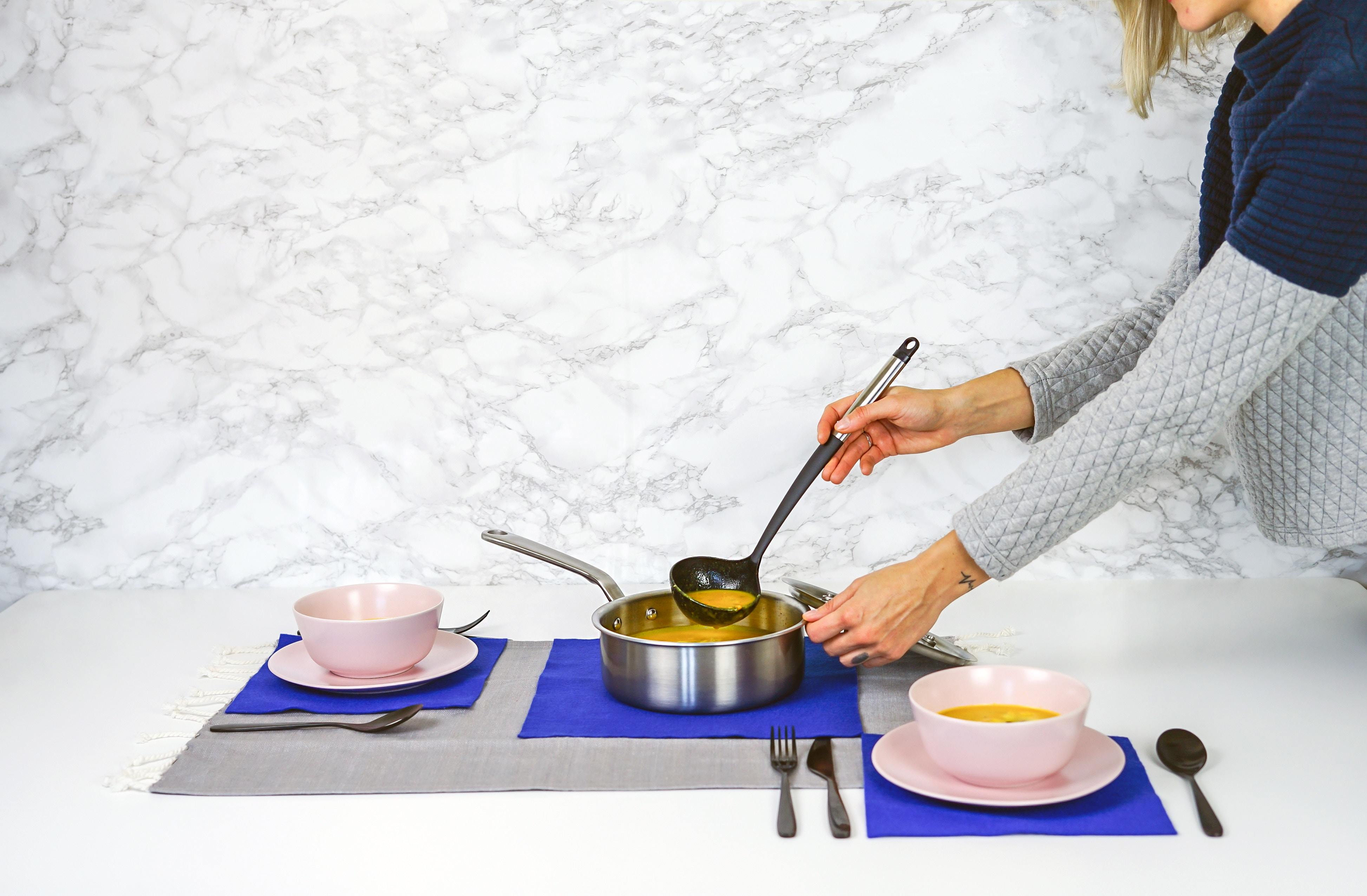 Frau richtet Suppe in zwei Schüsseln an.